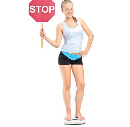 Girl on scale holding stop sign