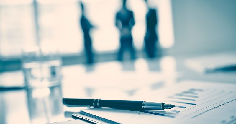 Fountain pen on business document, three men standing on background