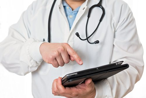 Physician updating patient chart on a tablet