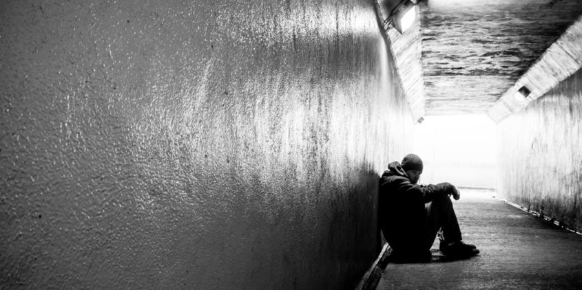 Teenager sits along, slumped on the ground in a pedestrian tunnel