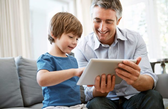 A father and his young son working together with a tablet