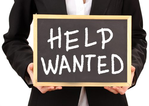 Close-up image of a man holding a Help Wanted chalkboard sign