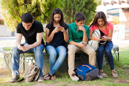 Group of teens sitting outside using cell phones and not talking to each other