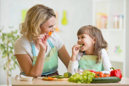 woman and young girl cooking together with fresh vegetables