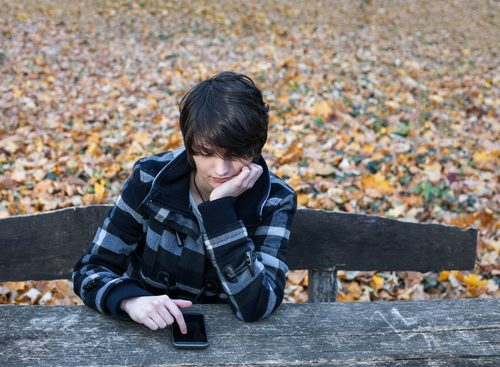 Lonely teen girl on cell phone sitting on bench.