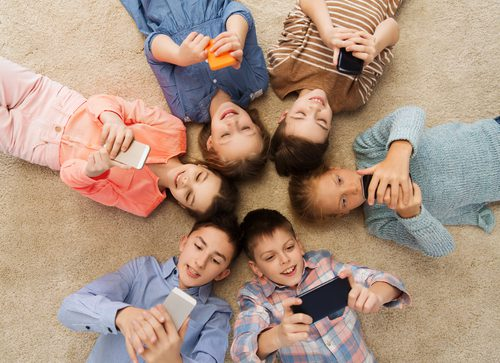 6 young girls and boys lying in a circle all on their smart phones