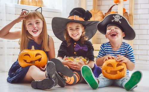 3 kids in Halloween costumes, sitting together with carved pumpkins